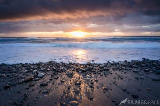 dramatic clouds and pounding surf at Sunset over the Tasman Sea, from Gentle Annie Beach, West Coast.  New Zealand landscape photography by Todd Sisson.